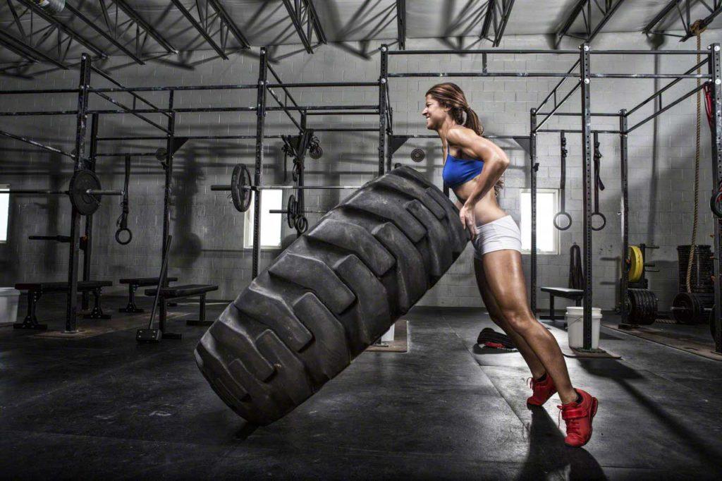 CrossFit athlete flipping a tire --- Image by © Artiga Photo/Corbis